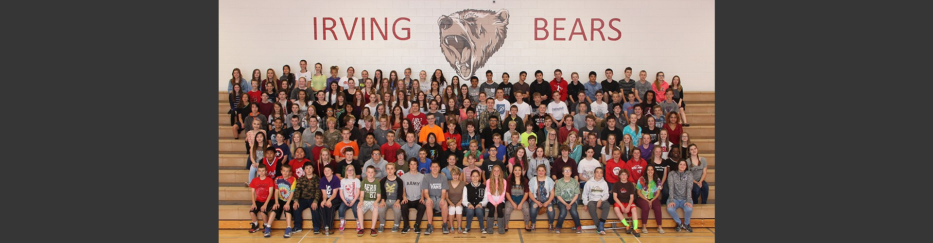 8th grade Irving Middle School students posing on bleachers under Irving Bears logo